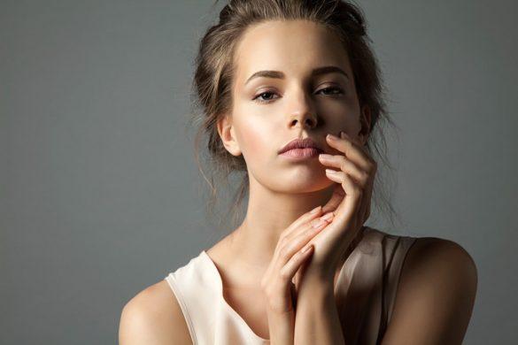 Viso e collo di una donna giovane bionda che ha un sguardo sereno sereno con la mano sinistra nel profilo sinistro del viso e con la mano destra sopra l'altra