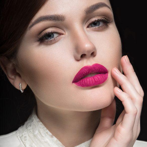 Foto di un bello viso di una donna con le labbra pink e sfondo nero, con la mano sinistra appoggiata sulla faccia